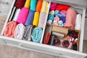 Image of folded clothes and items stored neatly in a dresser drawer