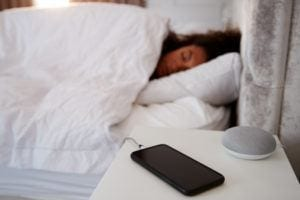 Woman Asleep with Virtual Assistant and Smartphone on Bedside Table