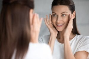 Well-Slept Woman Looking in the Mirror at her Beautiful Glowing Skin - Simply Good Sleep