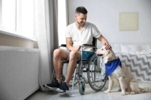 A man in a wheelchair patting his pet dog in his wheelchair accessible bedroom