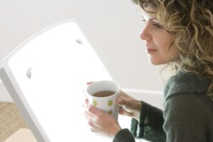 Woman sitting in front of bright SAD light therapy lamp while enjoying her morning cup of tea - Simply Good Sleep