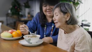 Female Caregiver Feeding Elderly Woman - Caregiver can benefit from Sleep Tips for Caregivers outlined in blog for amazing sleep - Simply Good Sleep